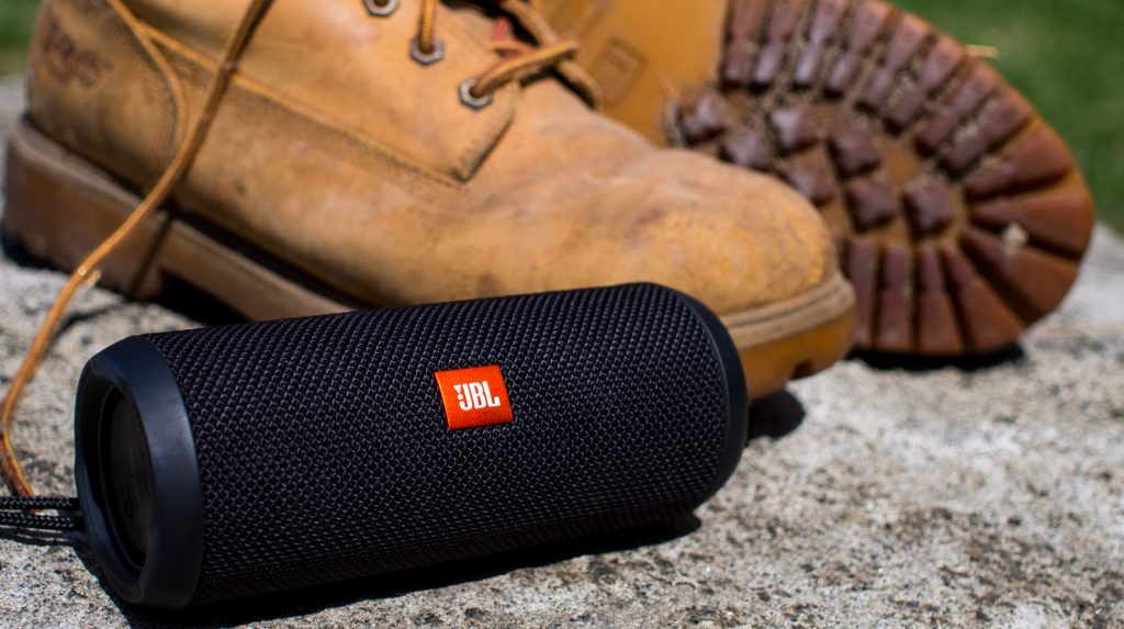A photo of the JBL Flip 3 Bluetooth speaker on the top of a mountain with boots in the background.
