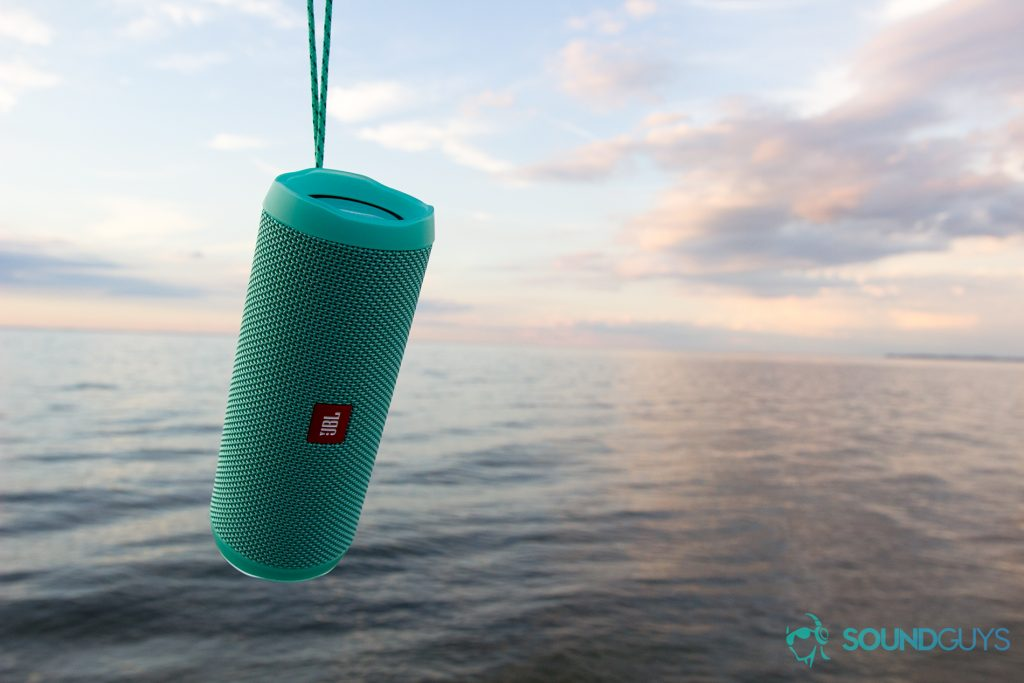 Pictured: The JBL Flip 4 speaker dangling over a body of water; skies are minimally cloudy around sunset.