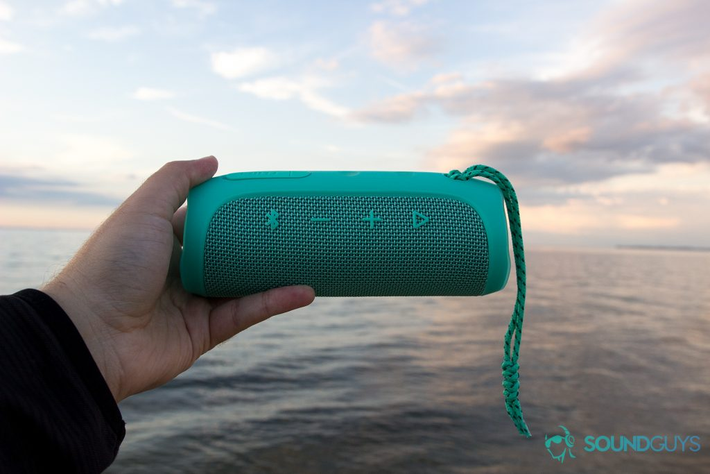 Man holding teal JBL Flip 4 in hand over the water with the playback buttons visible.