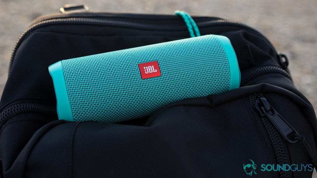 waterproof speakers: The JBL Flip 4 in aqua blue. It's in a black duffle bag on a beach at sunset.