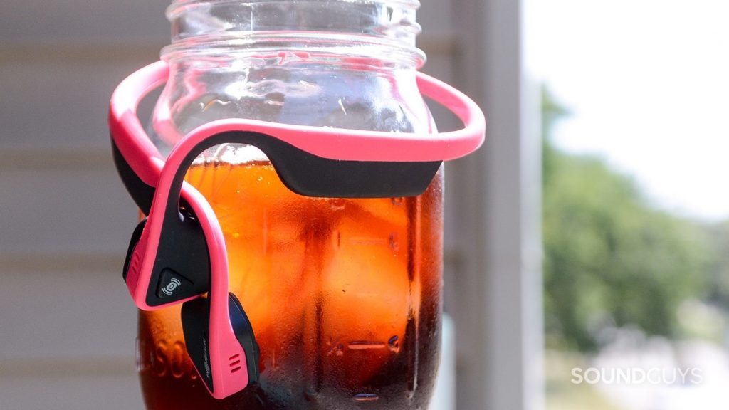 The headphones gently wrap around your head making and feel like a cozy hug. Pictured: The Aftershockz Trekz Titanium wrapped around a cold brew coffee. These are the safest Bluetooth headphones for running.