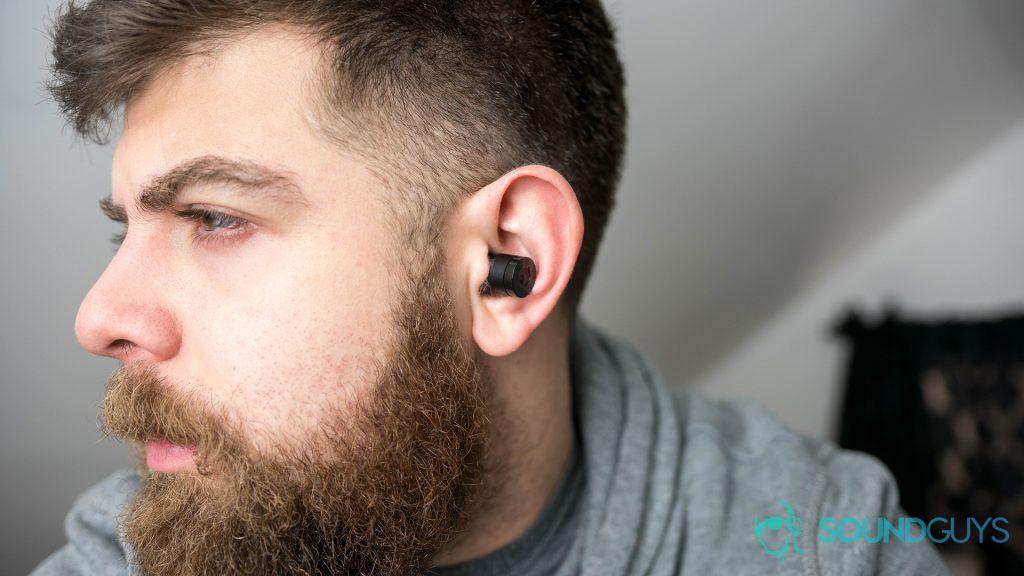 A photo of a man wearing true wireless Bluetooth earbuds.