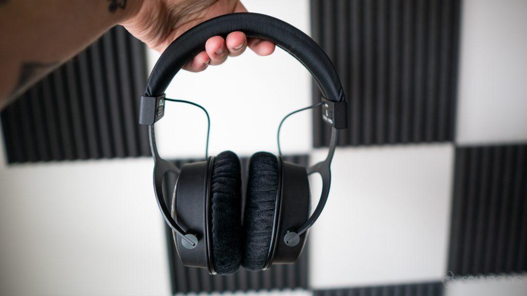 The Beyerdynamic DT 1990 Pro headphones in front of foam paneling on walls.