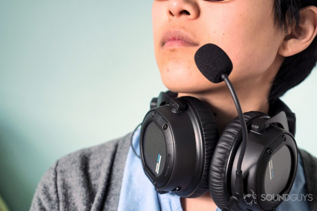 Beyerdynamic Custom Game gaming headsets being worn around the neck with the mic to the mouth.
