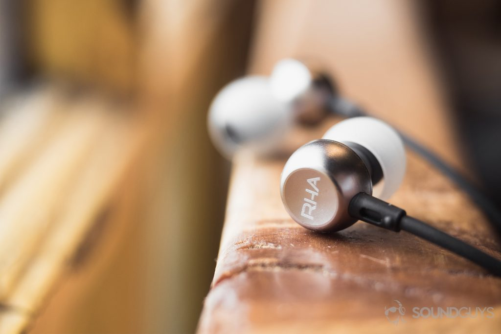 RHA MA390 review: The earbuds are placed on a railing--the closer one is facing away from the user to show off the RHA logo and other is directed toward the viewer but is slightly blurred.