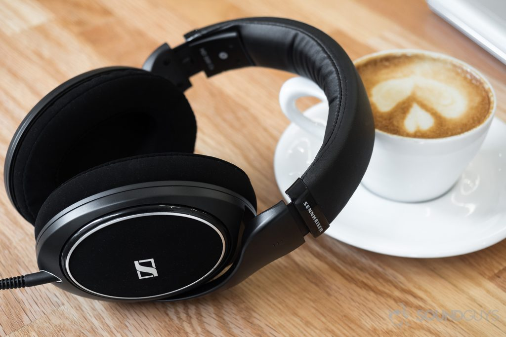 The headphones leaning against a cappuccino on a light-colored wood table.