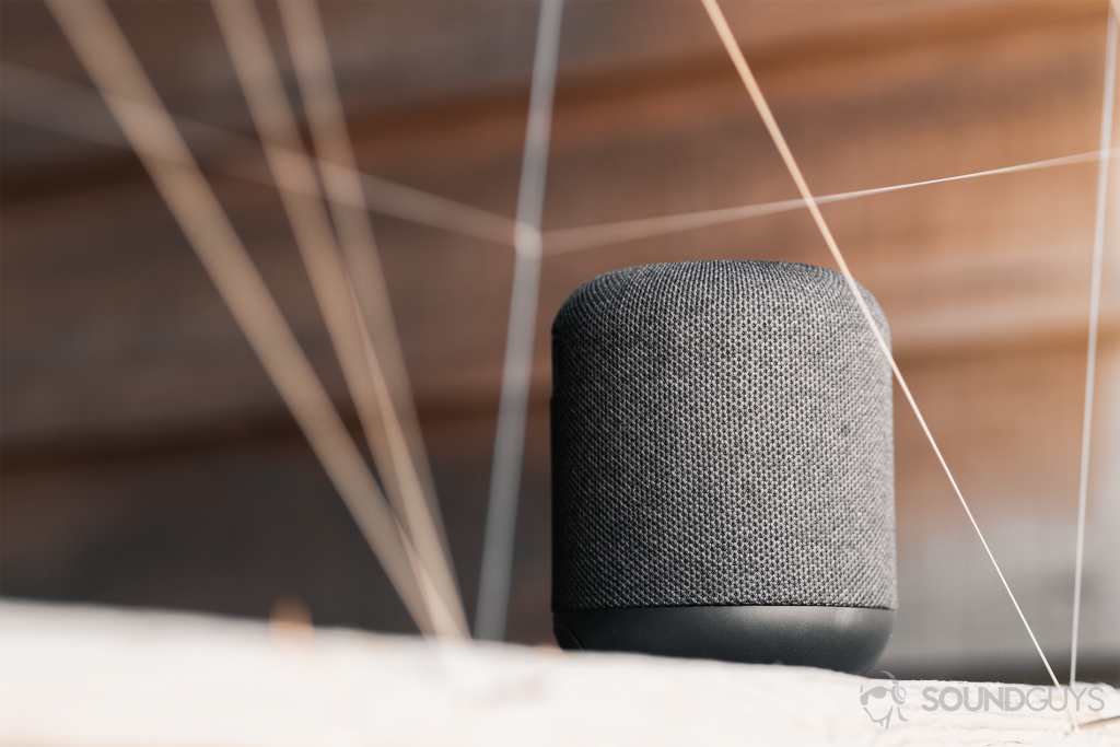 Best cheap Bluetooth speakers: An image of the speaker on a wood surface, against a horizontally paneled (wood) background.