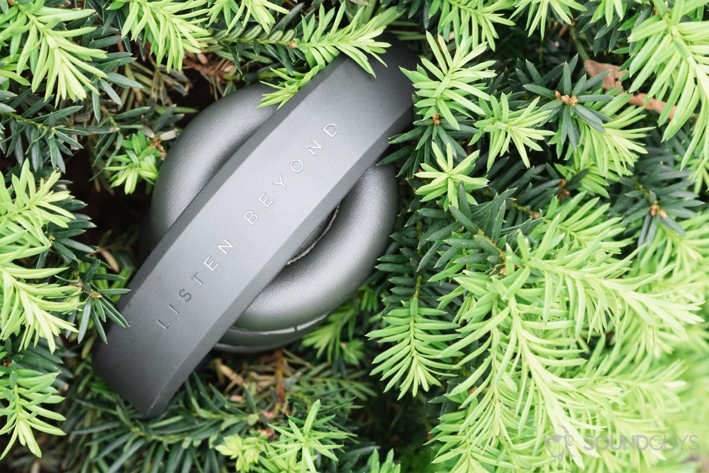 Focal Listen Wireless review: The headphones (olive) folded up and resting in a bright green shrub.