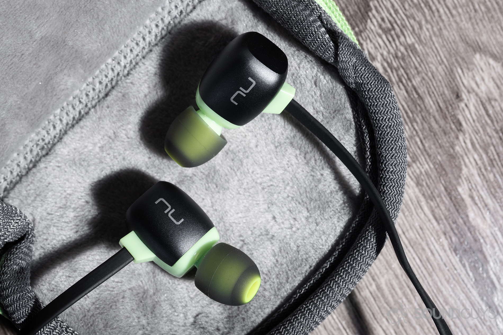 41f4523e46b Optoma NuForce Be Sport4: an overhead shot of the earbuds resting in the  included carrying