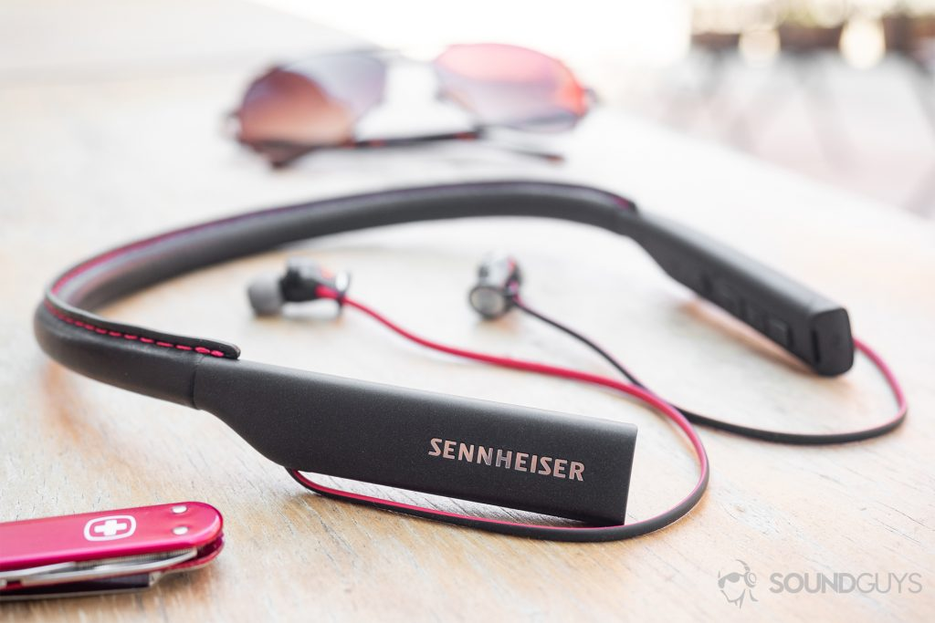 Sennheiser HD1 In-Ear Wireless: The earbuds on a wood table with sunglasses in the background and a Swiss Army knife in the foreground.