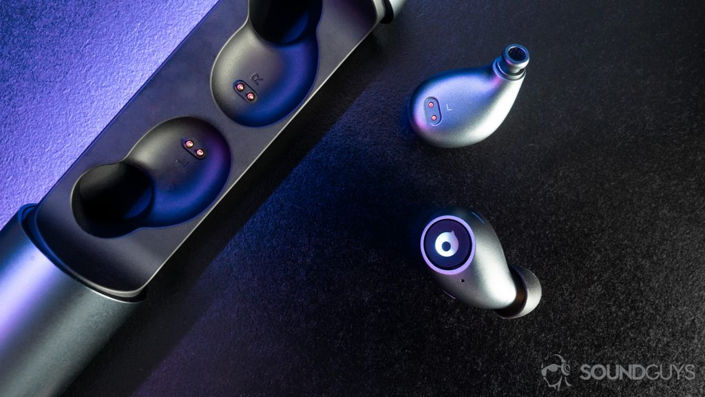 A top-down image of the earbuds with purple lighting on a black surface.