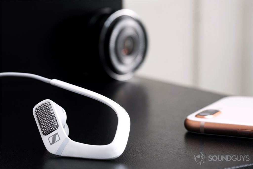 Sennheiser Ambeo Headset: The right earbud in the foreground (left) with an iPhone 8 Plus on the poking in from the right side of the image. An olympus lens is in the background.