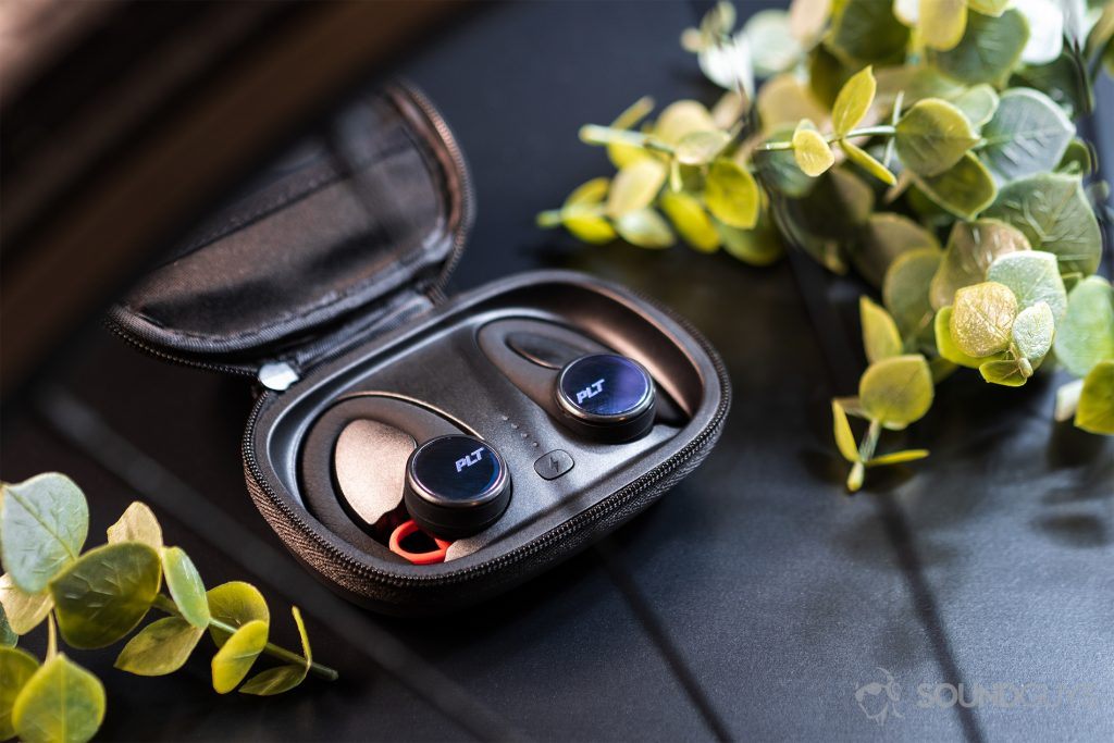 A picture of the Plantronics BackBeat Fit 3100 earbuds in the case, which lays open, and flanked by two faux greenery pieces.