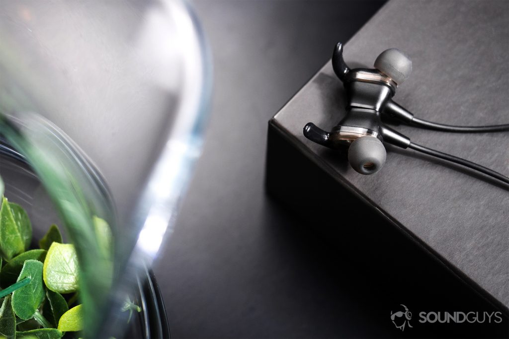 SoundPeats Engine: Top-down image of the earbuds magnetized together. The left half of the image depicts part of a glass vase.