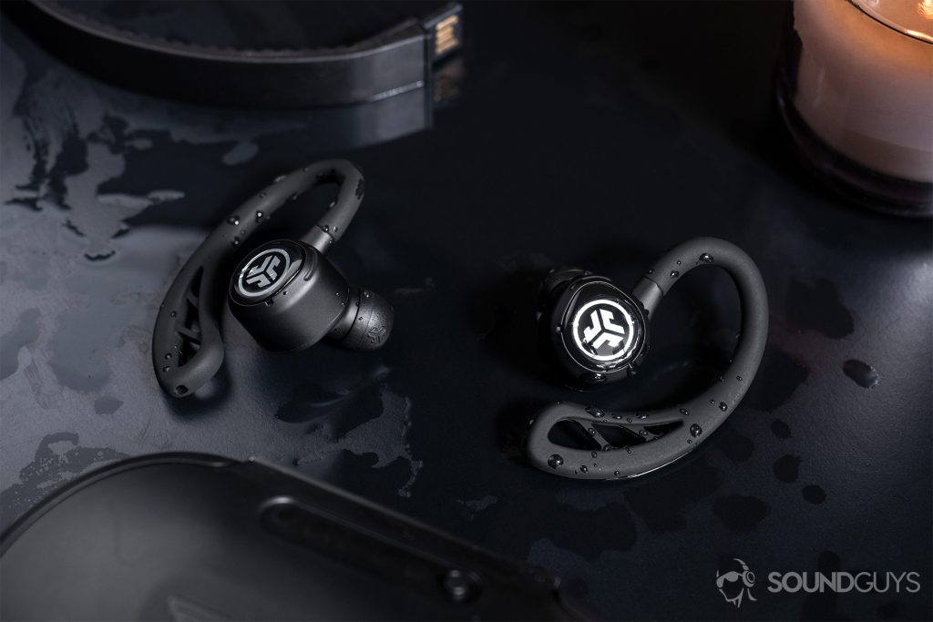 running headphones: The JLab Epic Air Elite earbuds surrounded by water on a black table.