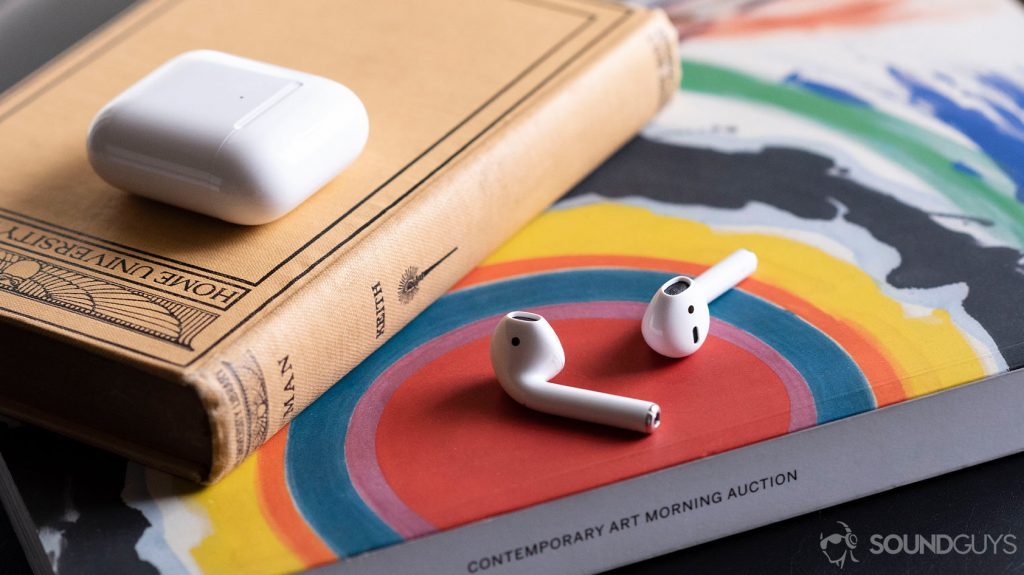 The Apple AirPods 2019 on an arts magazine with the case above it, shut.