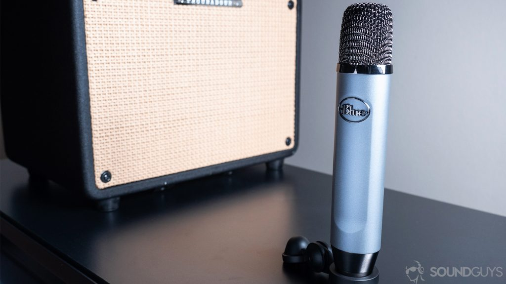 Blue Ember: The mic resting on a table in front of a guitar amp on a black surface.