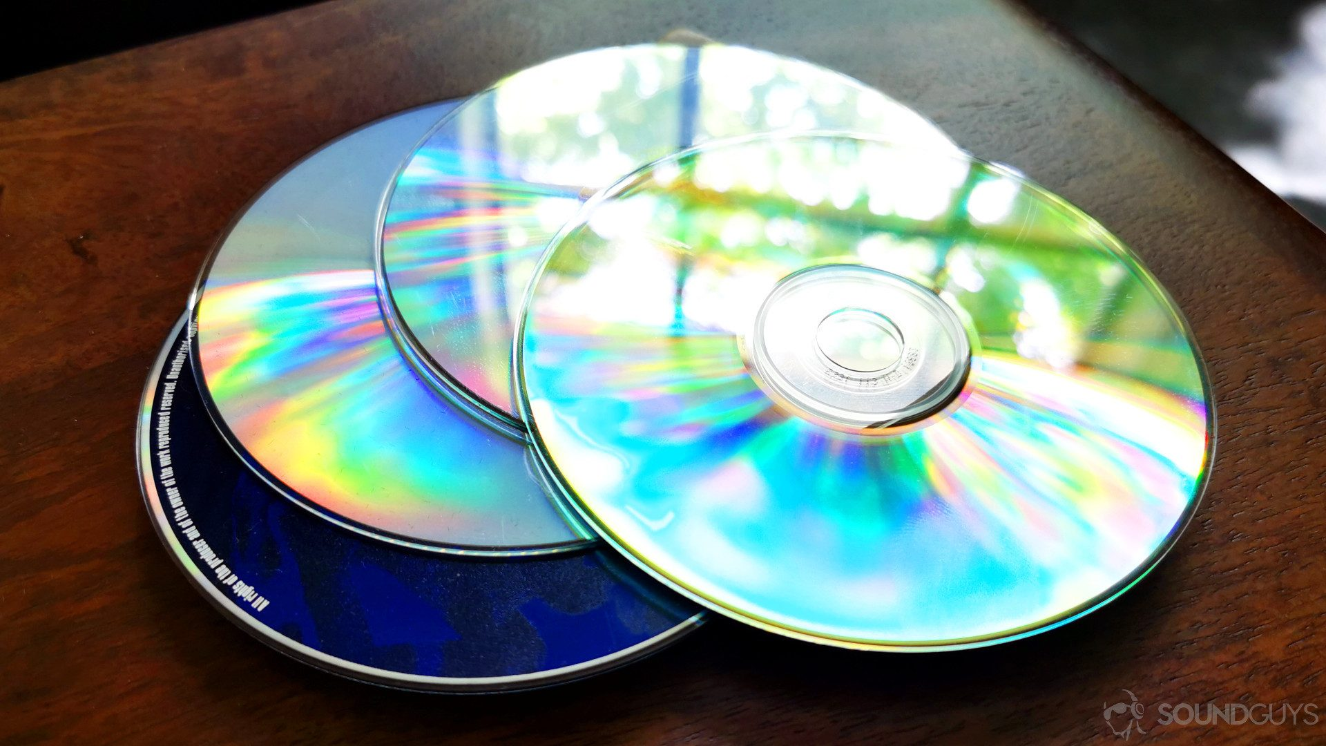 A photo of a stack of CDs on a wooden table - comparing cd quality bit-depth