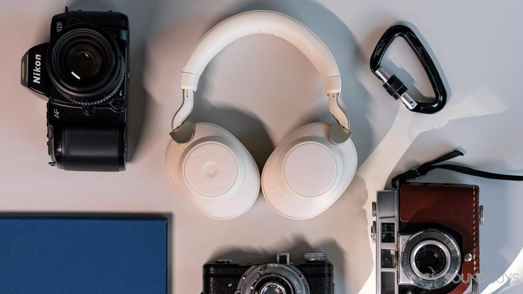 AKG N700NC - Jabra Elite 85h: Aerial image of the headphones folded flat on a table and surrounded by vintage cameras, a blue notebook, and a black carabiner.
