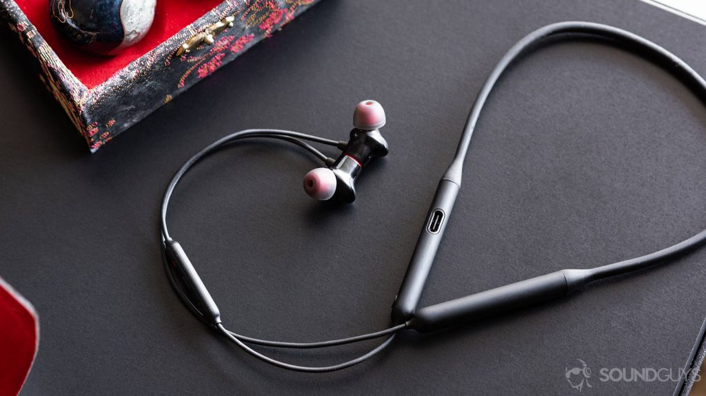 A picture of the OnePlus Bullets Wireless 2 earbuds and neckband with the cable curling up and around on a black table.