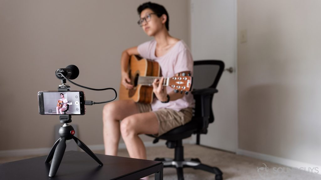 Woman playing guitar in front of the Shure MV88+ microphone attached to a Samsung Galaxy S10e smartphone: how to choose a microphone