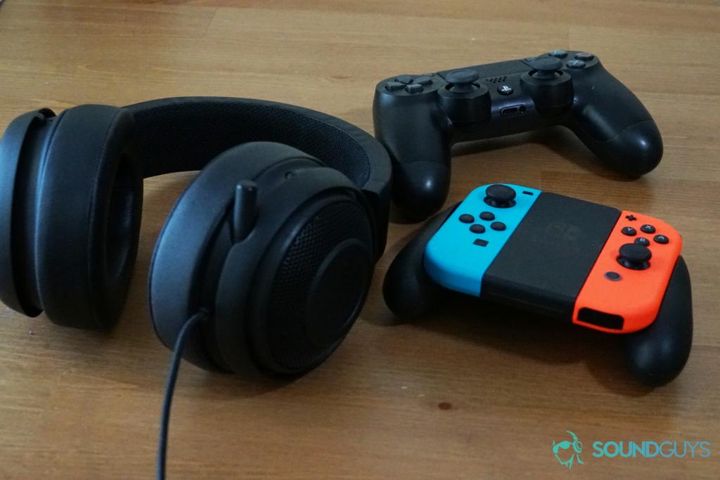 A photo of the Razer Kraken Pro V2 alongside Nintendo Switch, Sony PlayStation 4 controllers.