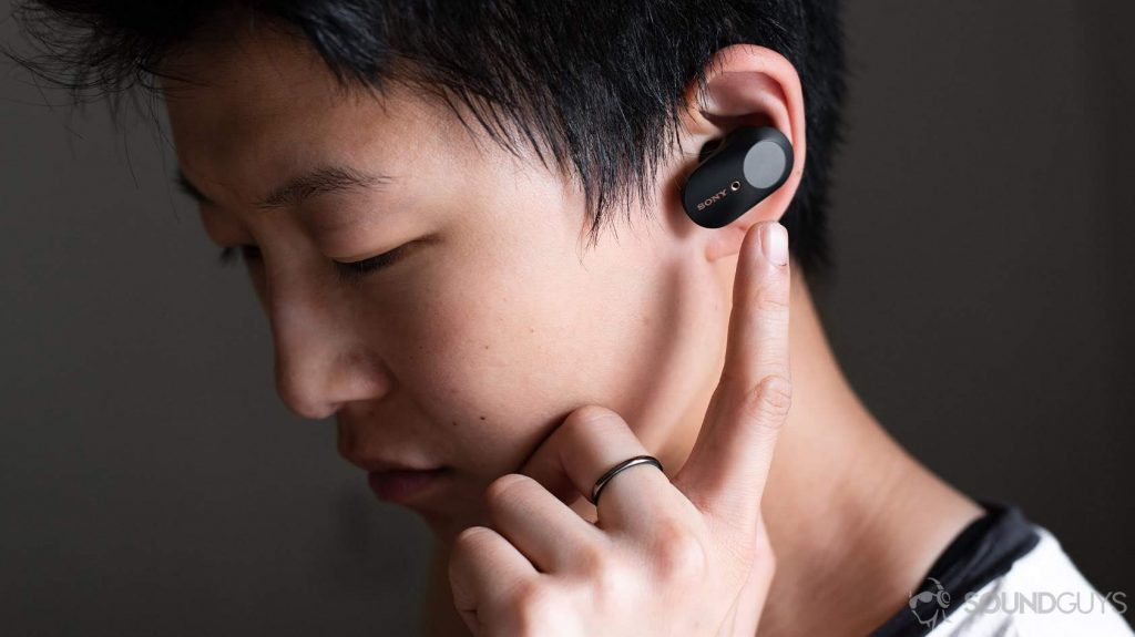 A picture of a woman wearing the Sony WF-1000XM3 earbuds and reaching for the touch panel of the left 'bud.