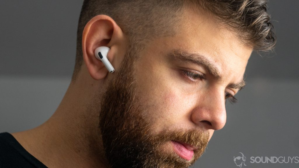 A picture of a man wearing the Apple AirPods Pro against a gray background.