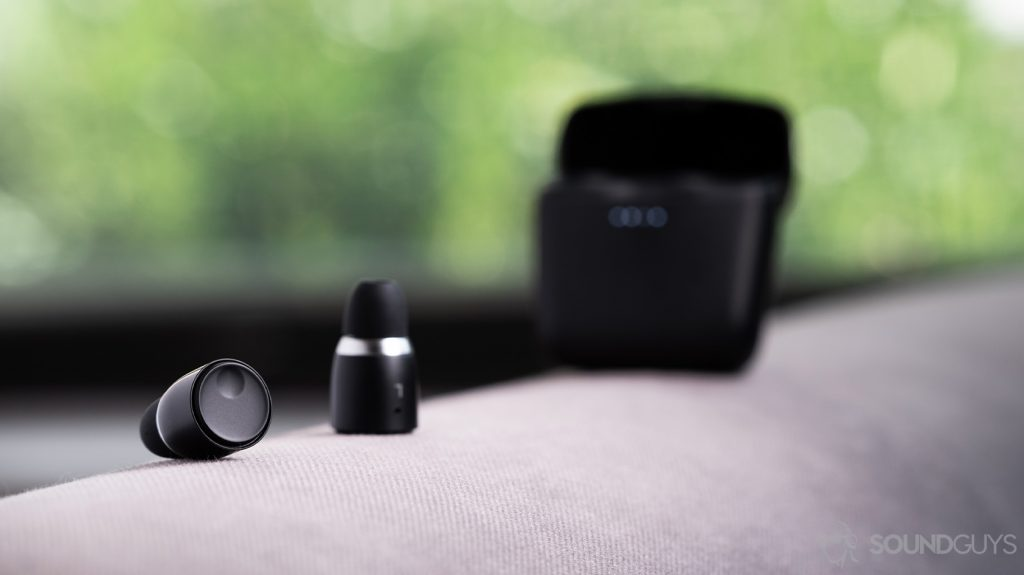 An image of the Cambridge Audio Melomania 1 true wireless earbuds outside of the case and in focus. The charging case is out of focus and open in the background. Both objects are on a cloth surface.