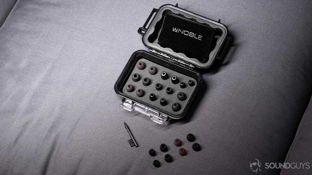 An angled, aerial photo of the Massdrop x Noble Kaiser 10 Universal Pelican carrying case open to reveal all included ear tips, an ear tip cleaner, and drawstring carrying pouch.