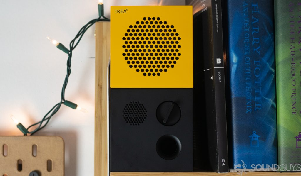 The IKEA x Teenage Engineering Frekvens speaker in yellow on a bookshelf next to Harry Potter books and Christmas lights