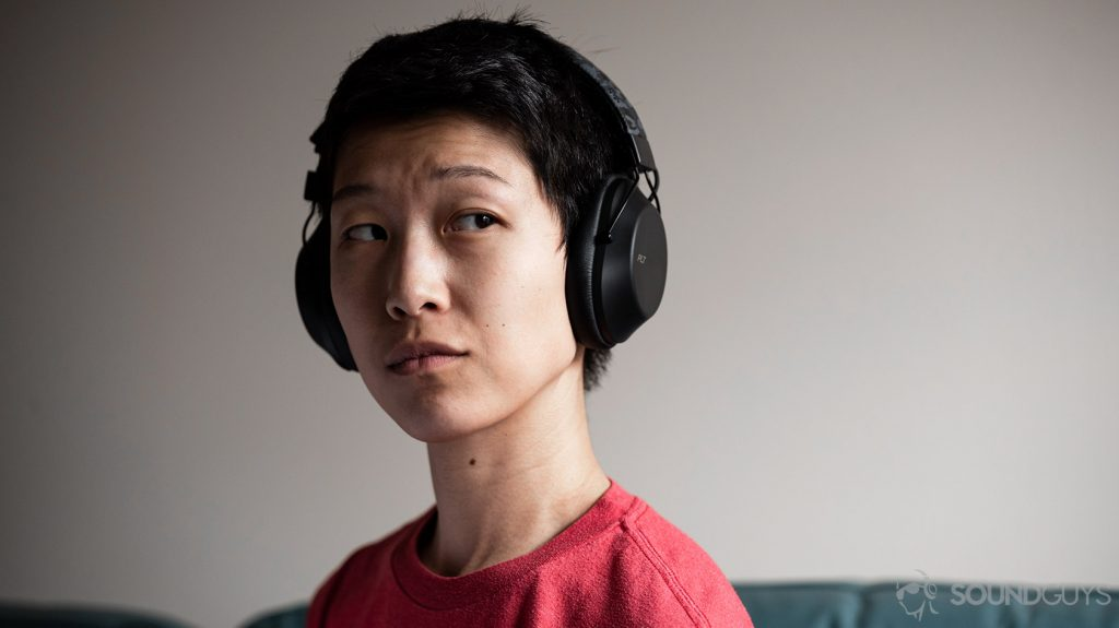 A picture of the cheap wireless headphones, Plantronics BackBeat Fit 6100, worn by a woman against an off-white wall.