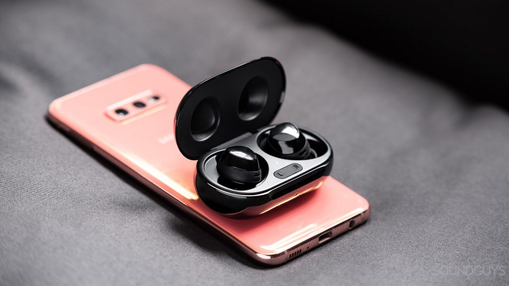The Samsung Galaxy Buds Plus true wireless earbuds on top of a Samsung Galaxy S10e smartphone in flamingo pink.