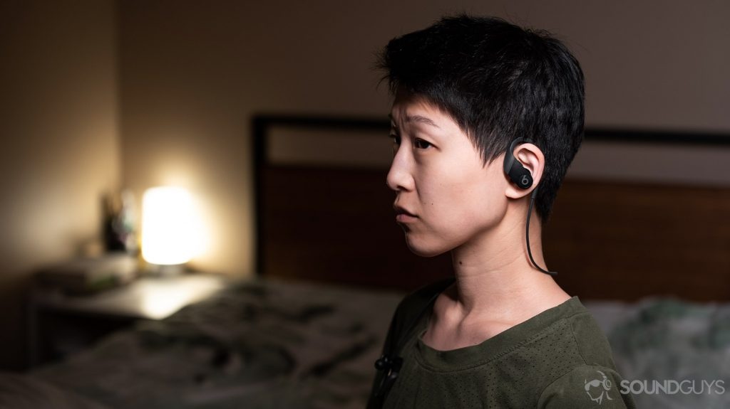 A picture of a woman wearing the Apple Beats Powerbeats workout earbuds in a bedroom.