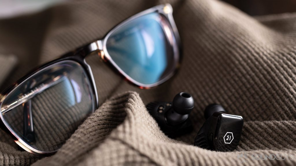 A picture the Master & Dynamic MW07 Go true wireless earbuds in front of Warby Parker tortoise shell glasses.