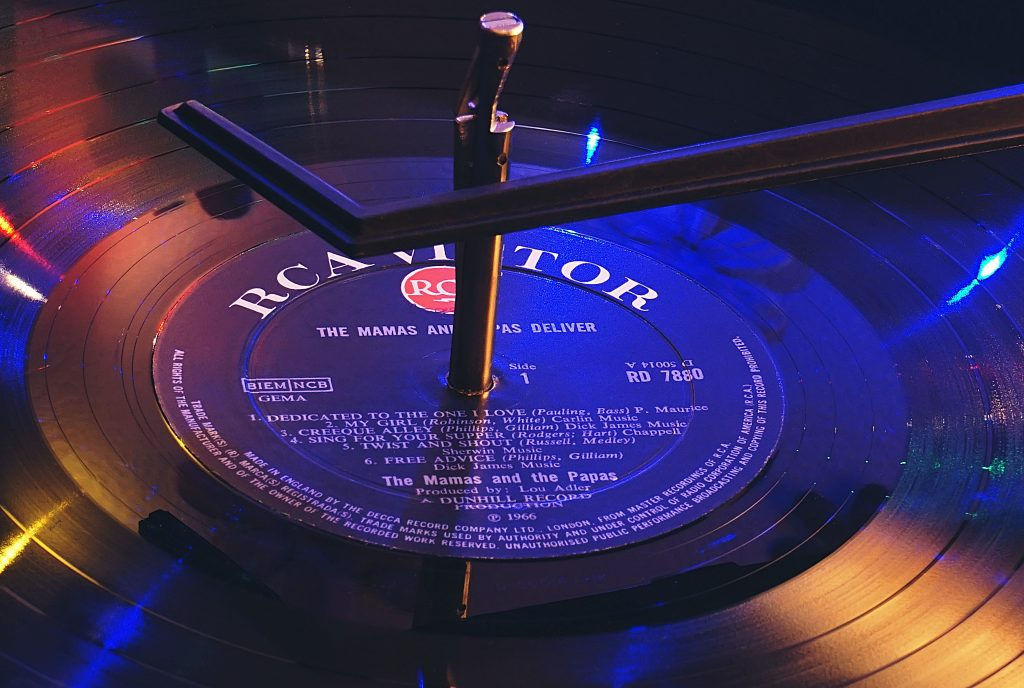 A photo of a vinyl record with a label and producer listed on the front; essential information for those looking how to find new music.