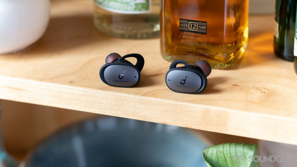 Anker Soundcore Liberty 2 Pro earbuds on shelf in front of liquor bottle.