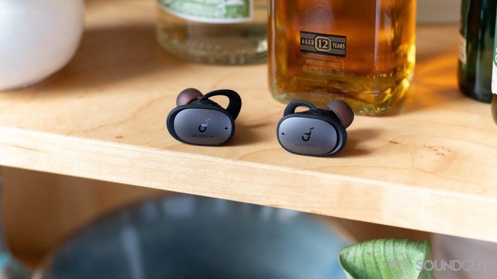 Anker Soundcore Liberty 2 Pro earbuds on shelf in front of liquor bottle.