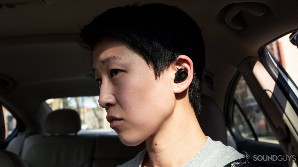 A picture of the Klipsch S1 True Wireless earbuds being worn by a woman in a parked car.
