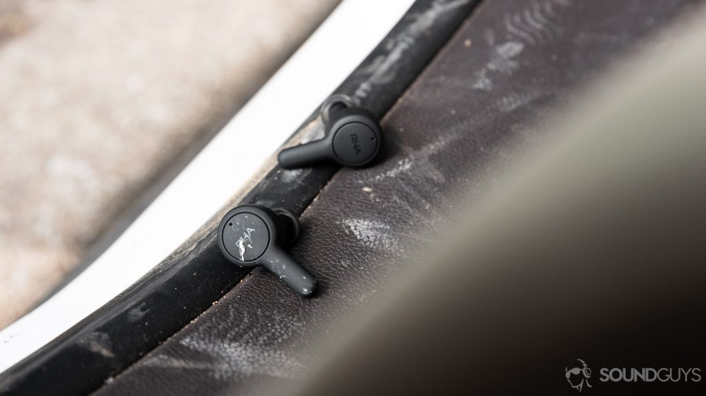 A picture of the RHA TrueConnect 2 true wireless earbuds on a dirty surface with dirt on the earbuds.