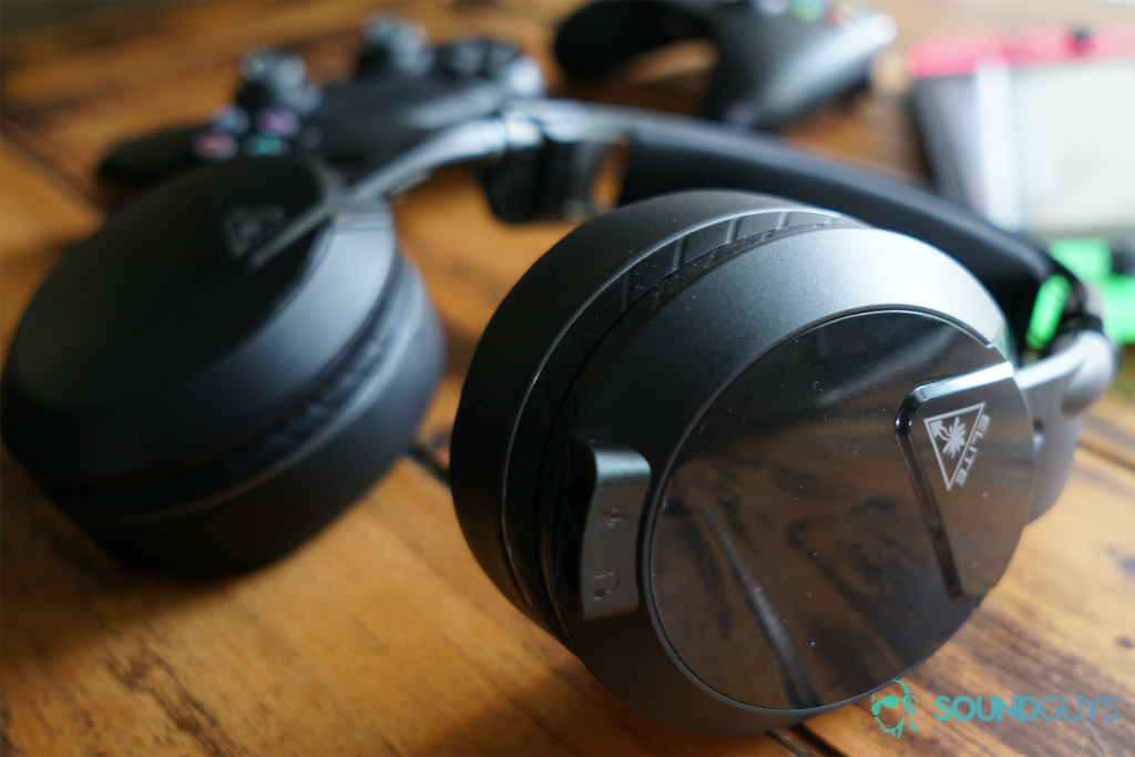 The Turtle Beach Elite Atlas gaming headset lays on a wooden table in front of a Nintendo Switch, Xbox One controller, and Playstation 4 Dualshock controller.