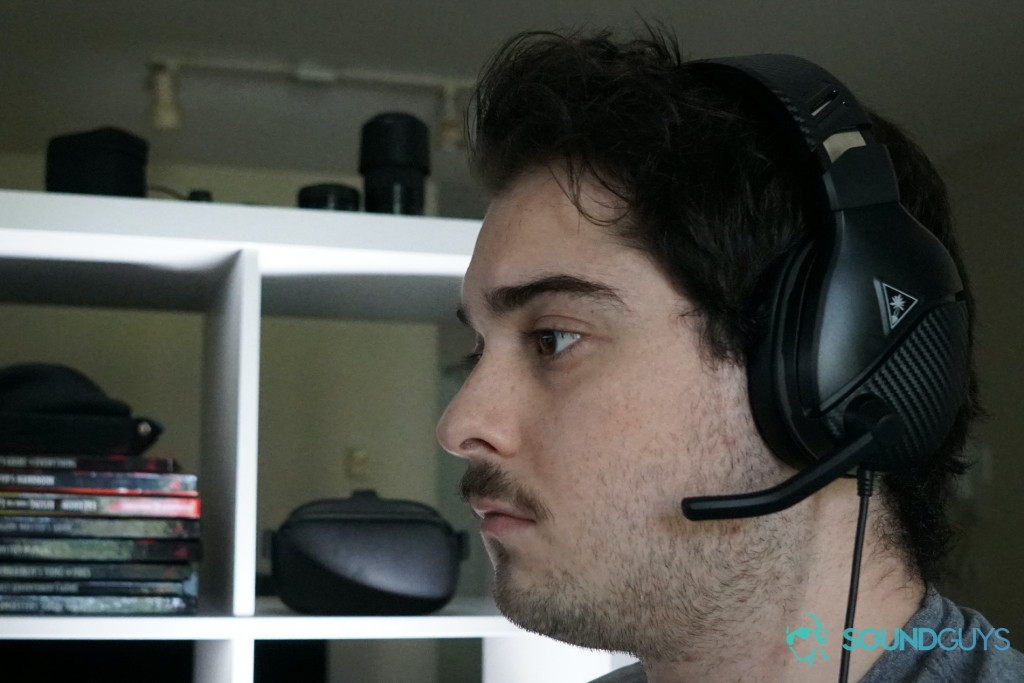 A man wearing the Turtle Beach Recon 200 sits near a shelf with Dungeons and Dragons books and an Oculs Quest on it