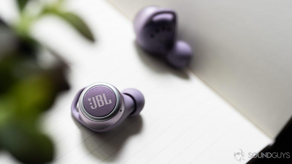 The JBL LIVE 300 TWS true wireless earbuds on a notebook.
