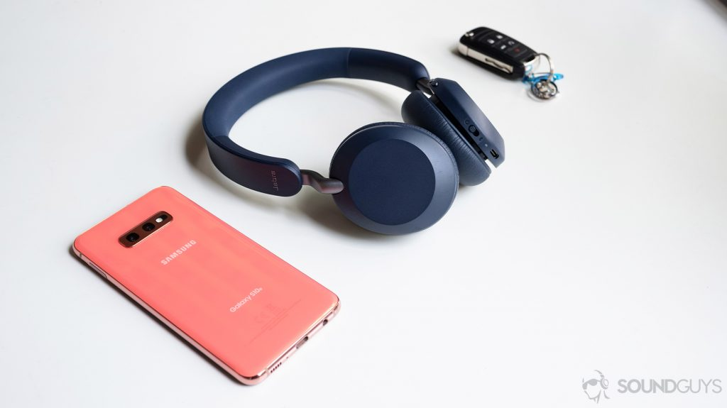 A picture of the Jabra Elite 45h on-ear Bluetooth headphones next to a Samsung Galaxy S10e smartphone and wireless car keys on a white table.