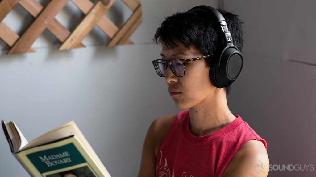 A picture of the Sennheiser PXC 550-II worn by a woman reading on a porch.