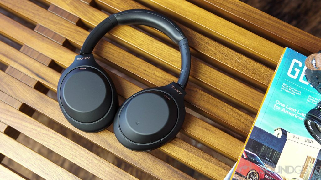 Sony WH-1000XM4 headphones next to magazines on a wood bench