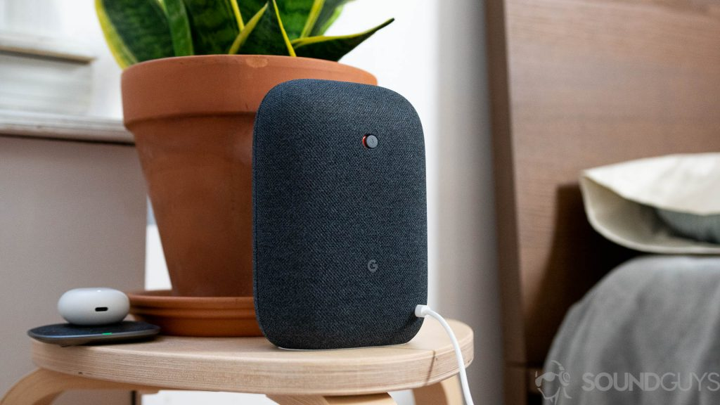Google Nest Audio in black on nightstand next to bed