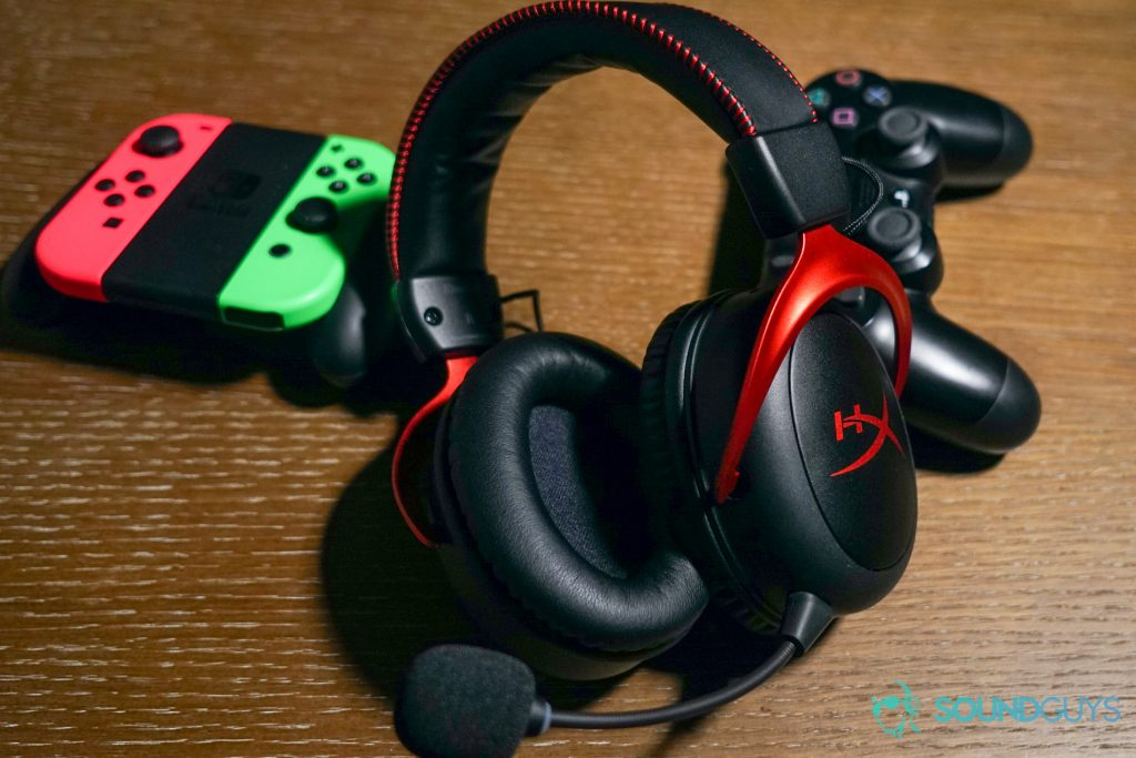 The HyperX Cloud II Wireless lays on a wooden table in front of a PlayStation 4 controller and Nintendo Switch Joy Cons.