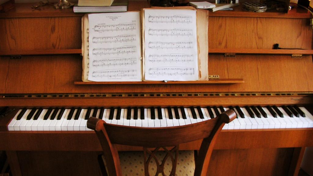 A light brown piano with sheet music on its stand. A chair is placed in front of the keys.