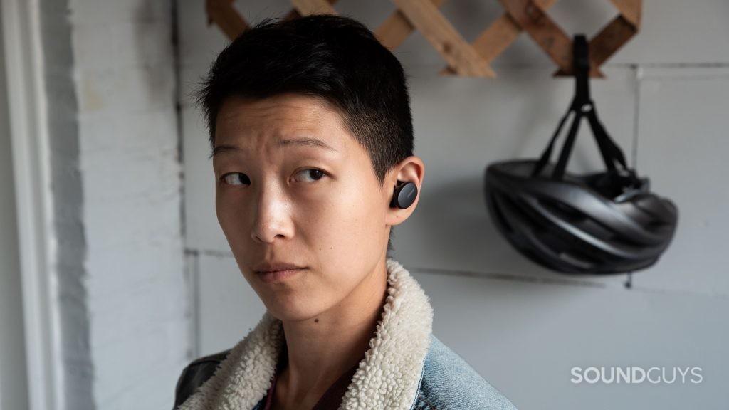A woman wears the Bose Sport Earbuds true wireless workout earbuds with a biking helmet in the background.